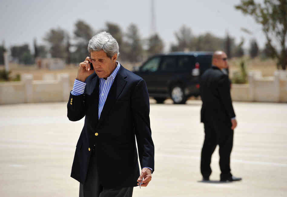 Secretary of State John Kerry speaks on the phone at Mafraq Air Base before boarding a helicopter to Amman on Thurs