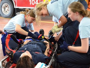 During a drill, teenage girls attending a firefighting camp secure their counselor, firefighter Clare Burley, for a basket rescue at Arlington County's fire station.