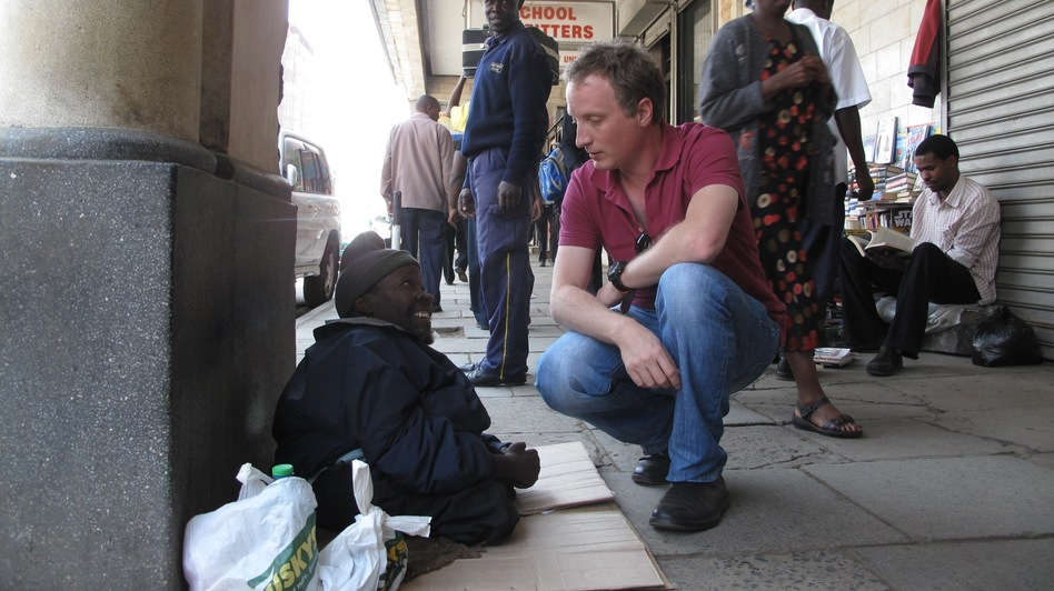 "Richard Crompton stops on the street to talk to ""George,"" a local supplicant and an inspiration for one of the characters in Crompton's first crime novel. Crompton says many of his characters are amalgams of people he met as a Nairobi journalist and resident. (NPR)"