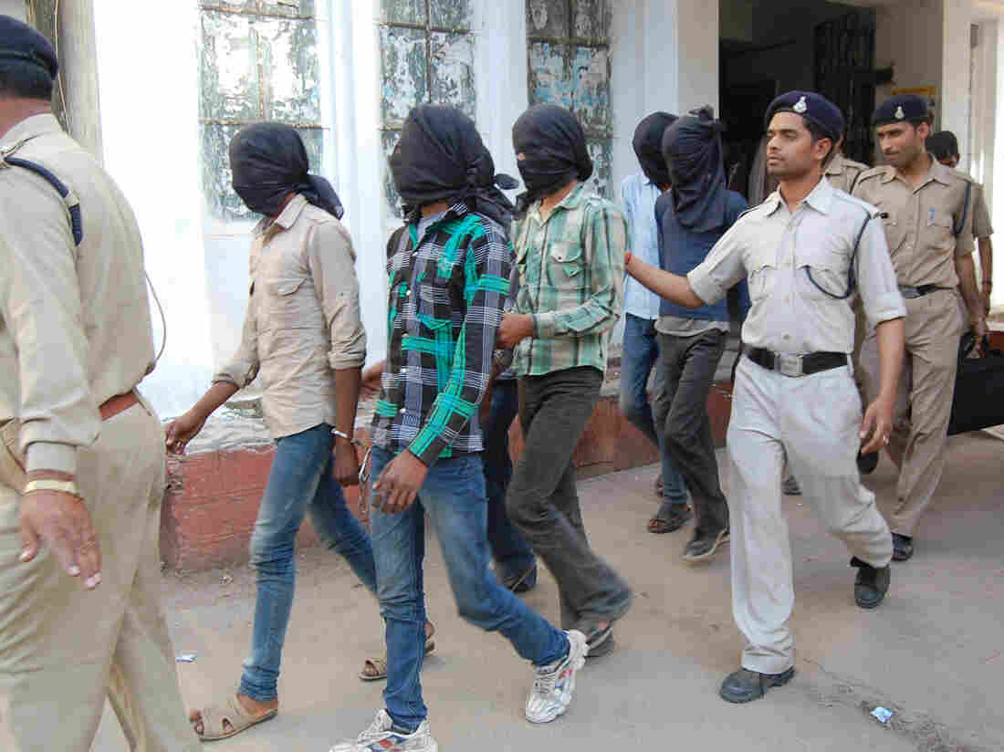 Indian policemen escort suspects in the rape case of a Swiss tourist to court in March. All six accused were sentenced to life on Saturday.