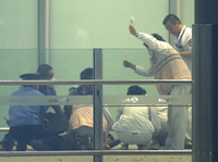 In a photo released by China's Xinhua News Agency, medical workers and policemen provide  assistance to the alleged  bomber at Beijing International Airport on Saturday.