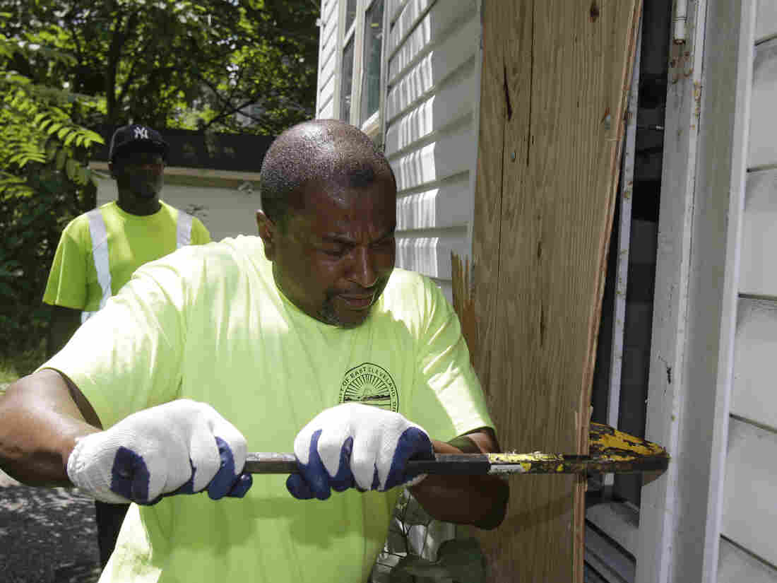 East Cleveland service department employee Ray Allen breaks into an abandoned house so searchers can enter on Sunday.
