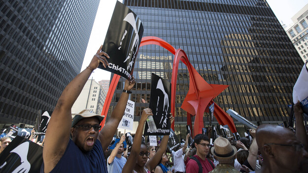 """A man holds up a sign at the """"Justice for Trayvon"""" rally in downtown Chicago on Saturday. (AP)"""