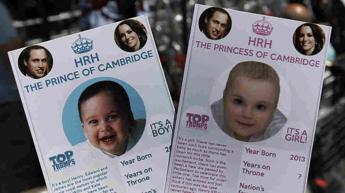 Cards depicting the 'royal baby' either as a boy or a girl, specially made by a games company as a publicity stunt are pictured, backdropped by members of the media waiting across the St. Mary's Hospital exclusive Lindo Wing in London on  July 11, 2013.