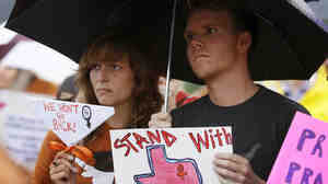 Becca Besaw of Austin, Texas, and Christopher Robertson of Fort Worth, Texas, protest the state's new law restricting access to abortion at a rally in Dallas on July 15.