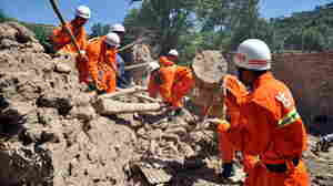 Rescuers clear debris Monday in China's Gansu province, where dozens of people were killed when earthquakes struck the region.