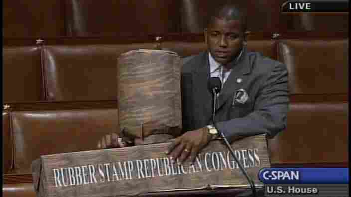 "Former Rep. Kendrick Meek (D-Fla.) holds a ""rubber stamp"" prop created mostly out of paper."