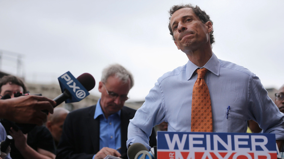 Anthony Weiner listens to a question from the media after courting voters outside a Harlem subway station in May. (Getty Images)