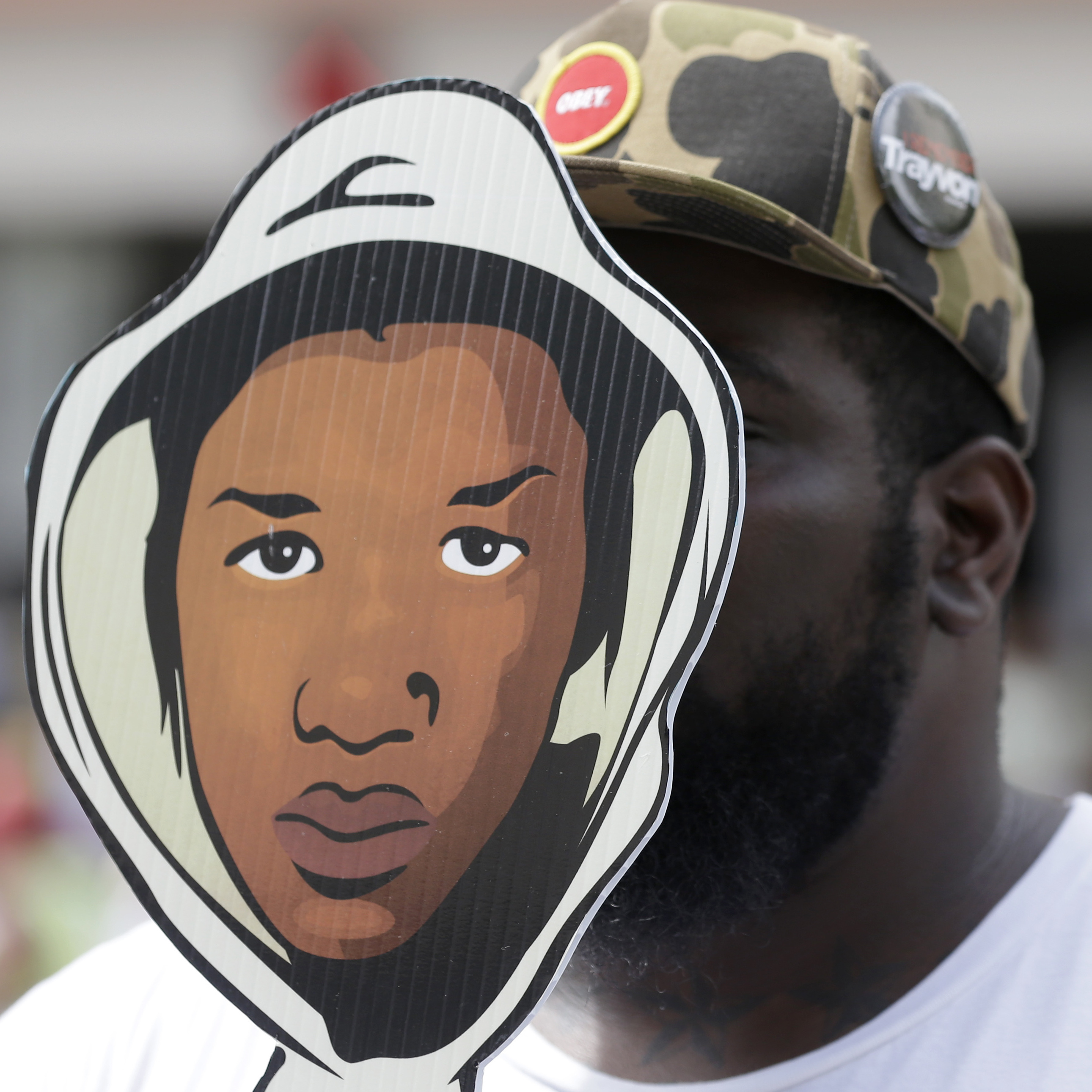Aqua Etefia holds up a Trayvon Martin mask at a rally Saturday in Miami.