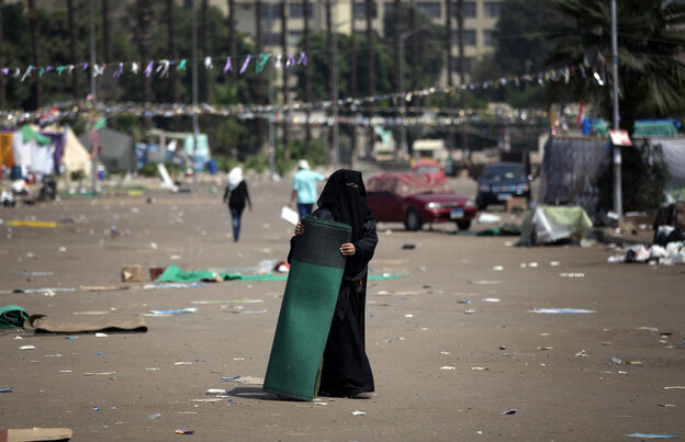 A supporter of Egypt's ousted President Mohammed Morsi holds a mat on Tuesday, where protesters have set up a camp near Cairo University in Giza, Egypt.