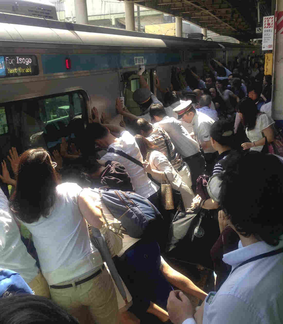 Train passengers and railway staff tilted a train car to one side as they rescued a woman Monday at a station near Tokyo. She had fallen between a the car and the platform. The woman was not seriously injured.