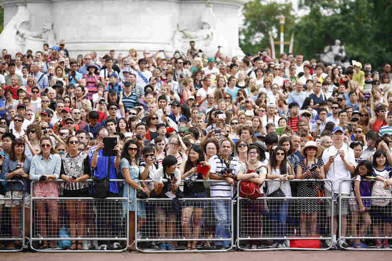 Crowds gather outside Buckingham Palace to read the easel displaying the announcement of the royal baby.