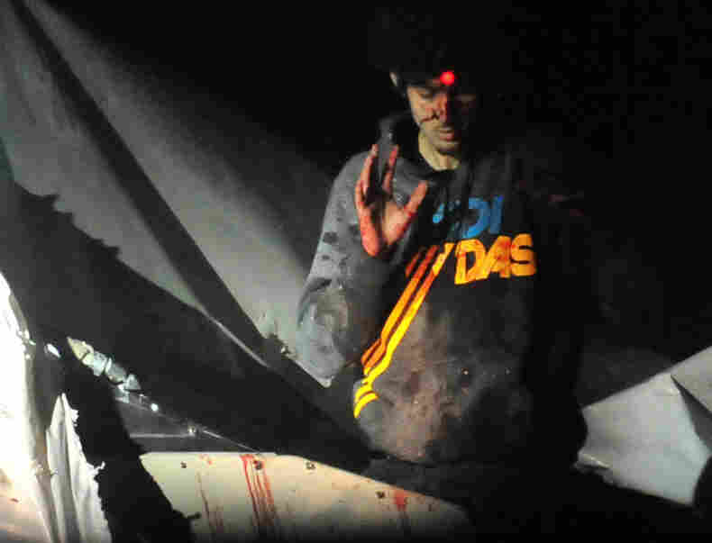 Boston bombings suspect Dzhokhar Tsarnaev emerges from a boat stored in a Watertown, Mass., backyard on April 19. The red dot of a police sharpshooter's laser sight can be seen on his forehead. This is among the images that Massachusetts State Police Sgt. Sean Murphy gave to Boston Magazine.