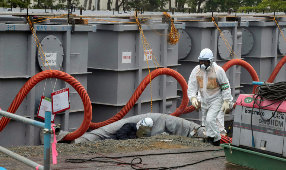 Tokyo Electric Power Co (TEPCO) workers work on waste water tanks at Japan's Fukushima Daiichi nuclear plant in the town of Okuma, Fukushima prefecture in Japan on June 12, 2013. (Noboru Hashimoto /AFP/Getty Images)