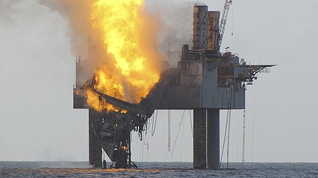 """An out-of-control natural gas well in the Gulf of Mexico continued to burn Wednesday after it blew out and caught fire. Beams supporting some of the """"Hercules 265 jack-up rig"""" have collapsed."""