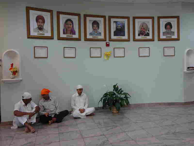 Framed photos of the six shooting victims of last August's shooting hang in the temple lobby.