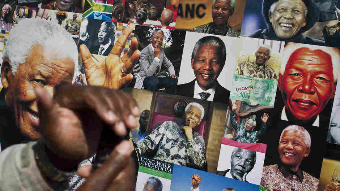 A well-wisher uses his phone to take a picture of a banner of photos of Nelson Mandela outside the Mediclinic Heart Hospital in Pretoria, where the former South African president is being treated.