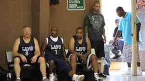 Los Angeles police officers take a break during a basketball game with residents of the Nickerson Gardens housing project in July 2011. Violent crime at Nickerson Gardens and two nearby housing projects has fallen by almost half since 2010.