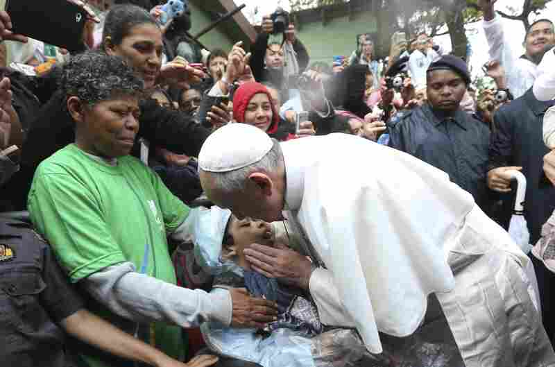 The pope blesses a child in the favela.