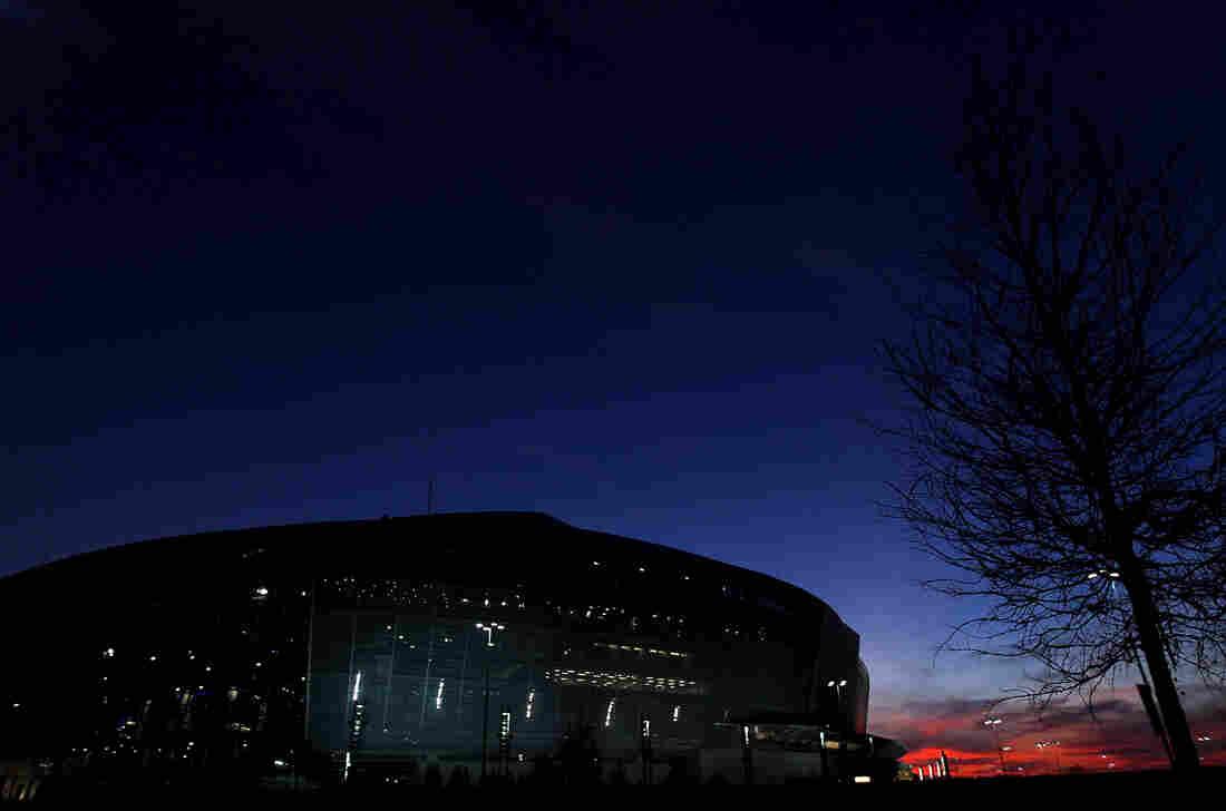 The sun sets behind Cowboys Stadium in Arlington, Texas.