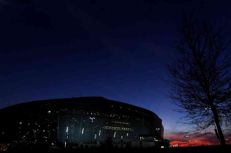 The sun sets behind Cowboys Stadium in Arlington, Texas.
