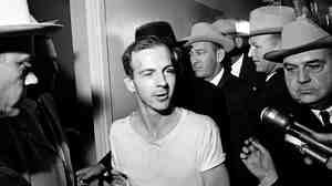 Lee Harvey Oswald, the assassin of President Kennedy in 1963, had defected to the Soviet Union several years earlier, but returned to the U.S. after becoming disillusioned with that country. He is shown here in a Dallas police station after his arrest for Kennedy's shooting.