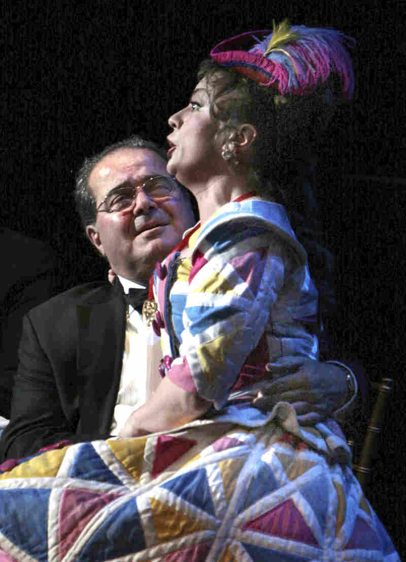 Justice Antonin Scalia sits onstage with opera singer Lyubov Petrova on his lap during the Washington National Opera opening night performance of the Strauss opera Ariadne auf Naxos on Oct. 24, 2009, at the Kennedy Center in Washington. Scalia played a party guest and sat onstage for the entire production.