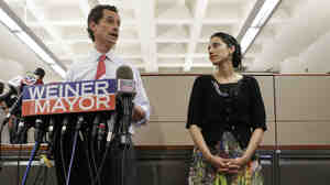 Huma Abedin (right) glances at her husband, New York City mayoral candidate Anthony Weiner, as he speaks at a press conference Tuesday.
