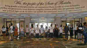 Protesters hold hands in the rotunda outside Florida Gov. Rick Scott's office after it closed for the evening last Friday.