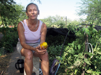 Food bank client Jamie Senik takes a break near her garden plot sponsored by the Community Food Bank of Southern Arizona. She grows food for herself and her diabetic mother.