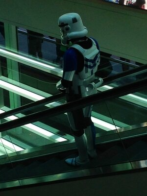 A lone, sad stormtrooper descends an escalator.