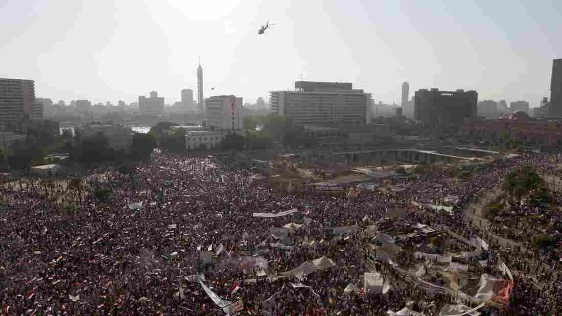 An Egyptian police helicopter flies over Tahrir Square, as protesters demonstrate in support of armed forces in Cairo on Friday.