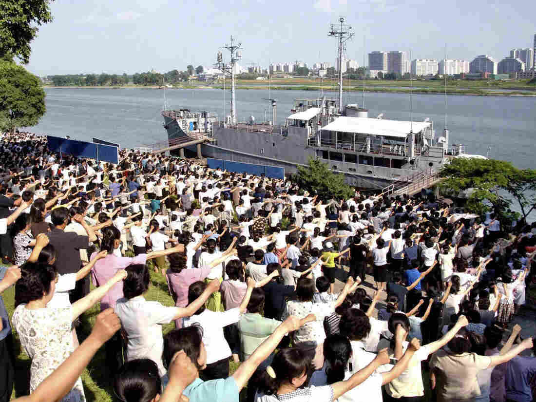 In a photo provided by the official Korean Central News Agency, North Koreans raise their fists in front of the USS Pueblo during a June rally in Pyongyang.