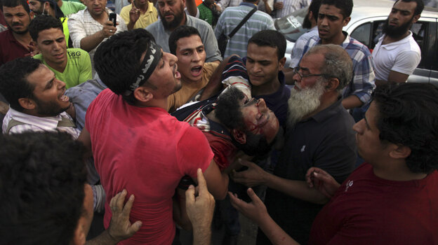 Supporters of Egypt's ousted President Mohammed Morsi carry an injured man to a field hospital follow