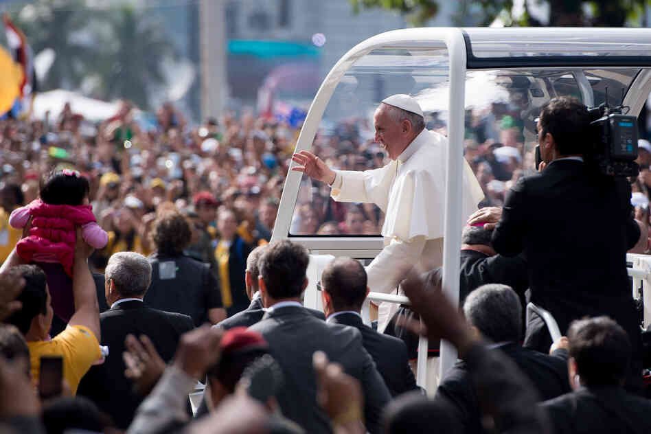 Pope Francis waves from the Popemobile as he heads to celebrate Mass for the Catholic Church's World