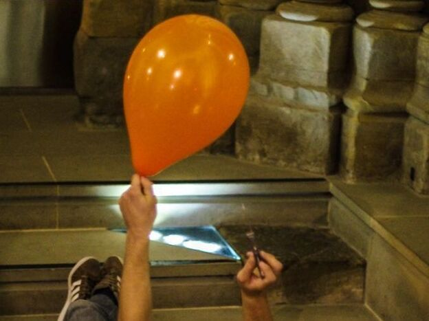 Researcher Ivan Dokmanic prepares to burst a balloon in the Lausanne Cathedral in Switzerland. By measuring the echoes made by the pop, he can calculate the shape of the room.