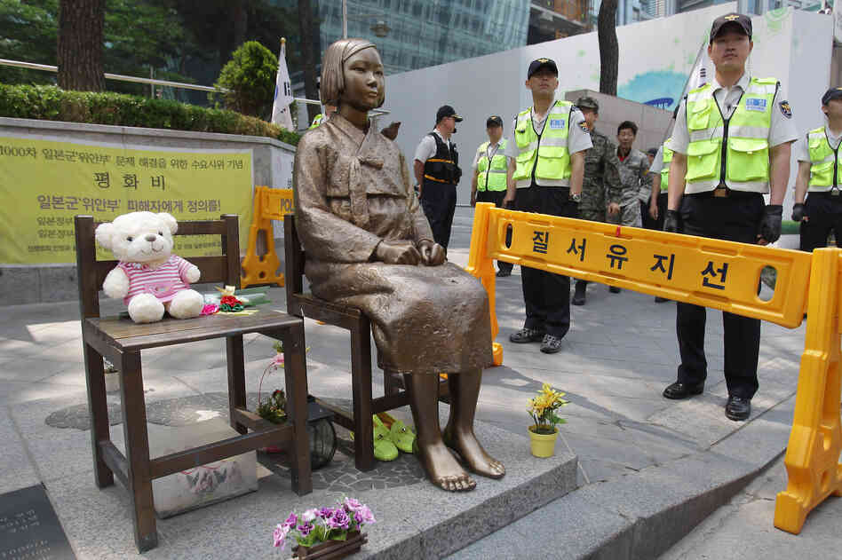 South Korean police stand guard beside a comfort woman statue in front of the Japanese embassy in