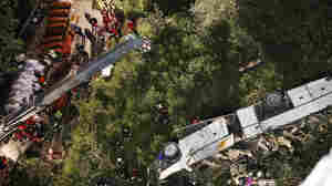 Rescuers prepare coffins for victims of a bus crash in southern Italy. At least 38 people died after a bus plunged off a highway and into a ravine.