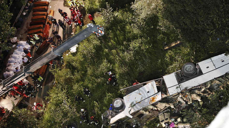 Rescuers prepare coffins for victims of a bus crash in southern Italy. At l