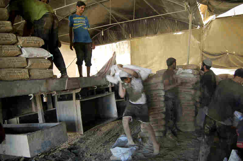 Workers in the Gaza Strip load a truck with sacks of cement that arrived via a smuggling tunnel from Egypt. Gazan officials say the Egyptian military has cracked down on smuggling tunnels that bring many goods into Gaza.