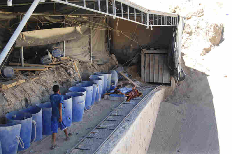 Gravel is slid underground in blue buckets and poured out for trucks to carry into Gaza. Israel strictly controls construction material entering the Gaza Strip.