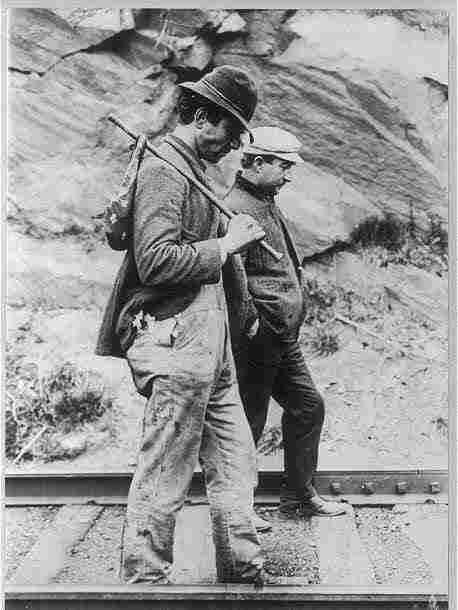 Two hobos walking the rails.
