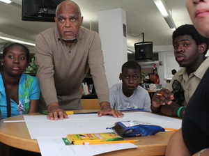 Bob Moses works with Jennifer Augustine, Guitoscard Denize, Darius Collins and other students who are part of this Algebra Project classroom. It's one of several student cohorts across the country where students who've struggled with math get to college-level by the end of high school.