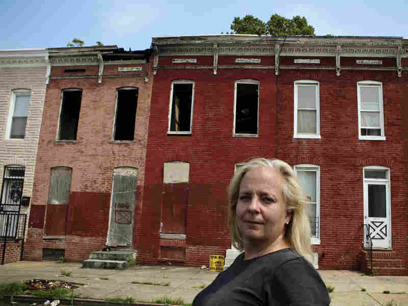 Carol Ott, who runs an anti-blight campaign called Baltimore Slumlord Watch, stands in front of a pair of vacant houses.