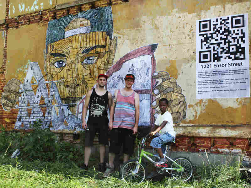 Ten-year-old Dareese Shelmon wandered over to help Nether and Tefcon put up the mural. The mural's finishing touch is a QR code that directs people to the name of the vacant house's owner.