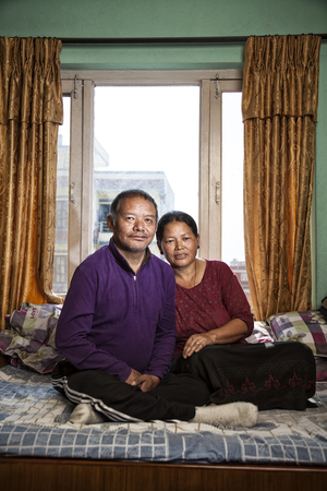 Ang Temba, 54, suffered a stroke on an Everest expedition in 2006. Against a doctor's advice, he went back to Everest in 2007 and had a second stroke shortly after returning. He's now confined to his bed and cannot speak. Here he sits with his wife, Furba, 48, in their Kathmandu, Nepal, apartment.