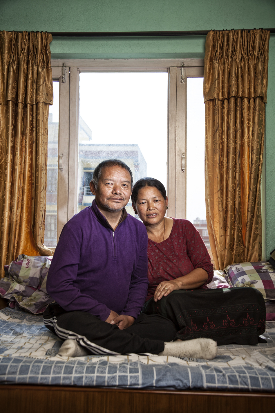 Ang Temba, 54, suffered a stroke on an Everest expedition in 2006. Against a doctor's advice, he went back to Everest in 2007 and had a second stroke shortly after returning. He's now confined to his bed and cannot speak. Here he sits with his wife, Furba, 48, in their Kathmandu, Nepal, apartment. (Courtesy of Grayson Schaffer)