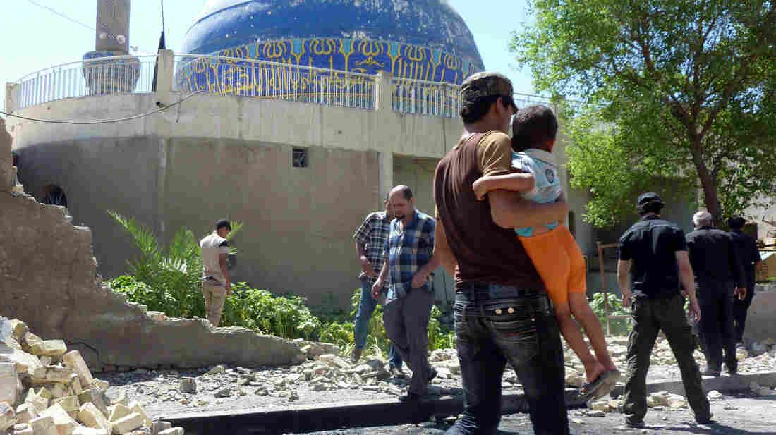 Iraqis walk past a wall that a car bomb destroyed, next to the Ahl al-Bayya' mosque in southeastern Baghdad Monday. At least 10 bombings were reported in the city today.