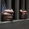A pair of hands gripping jail-door bars.