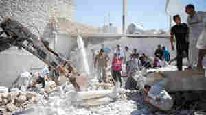Syrians search for survivors under the rubble of a destroyed house after a barrel bomb was dropped from an air force helicopter in Saraqeb on July 20.